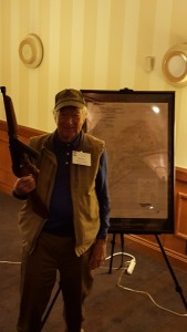 Veteran posing with Thompson SMG in front of map of Iwo Jima